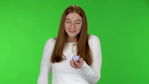 Portrait of Pretty Young Woman Is Opening a Small Box with a Surprise and Is Surprised and Rejoicing