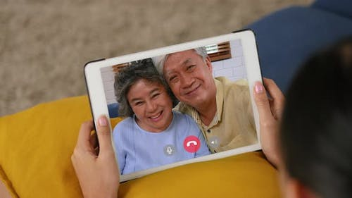 Young Asian grandchild having video chat with Grandfather and grandmother.