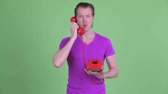 Thumbnail for Confused Young Man Using Old Telephone and Shrugging Shoulders