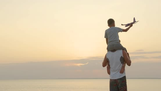 Thumbnail for Happy Father and Son Playing with Airplane Toy Together at Sunset Happy Family Walking Outdoors