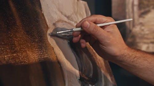 Hände des Künstlers ein männlicher Künstler malt eine Leinwand mit einem Pinsel