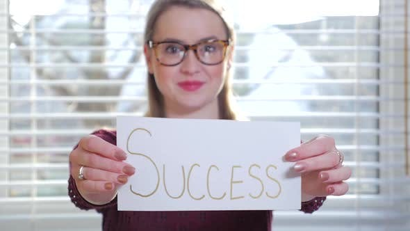 Thumbnail for A Young Blonde Female With Glasses Holding Up A Piece Of Paper That Reads Success 1