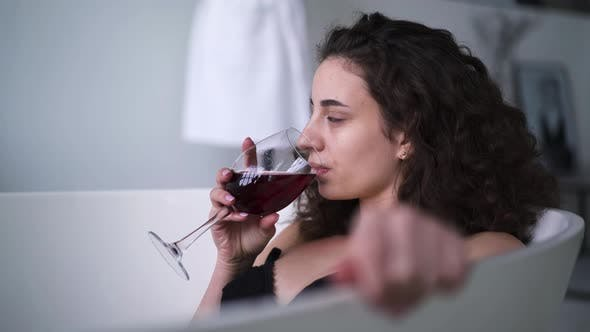 Thumbnail for Young Brunette Woman Drinking Red Wine in Bathtub. Side View Close-up of Confident Caucasian Girl