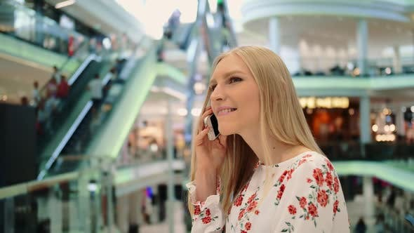 Thumbnail for Young Woman Speaking on Phone in Mall.