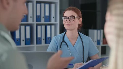 Cheerful Female Doctor in Medical Clothes and Glasses During Consultation with Married Couple in
