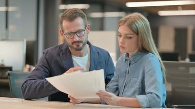 Businessman and Businesswoman Discussing Documents in Office