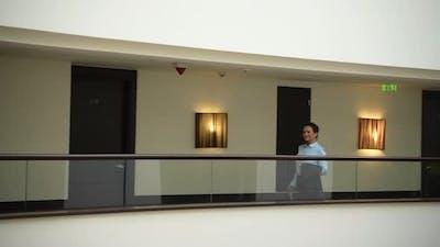 Cheerful Female Walking on Balcony in Luxury Hotel
