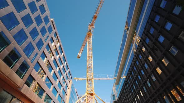 Thumbnail for A Large Tower Crane in the Downtown of the Modern City. Glass Office Buildings Around. Low Angle