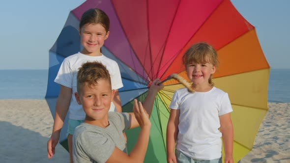 Thumbnail for Happy Children Spinning with Umbrella on Beach. Rainbow Umbrella. Sunny Day.