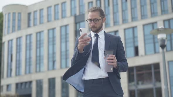 Thumbnail for Portrait of Concentrated Nerd Businessman Using Smartphone Outdoors in Front of Office Business