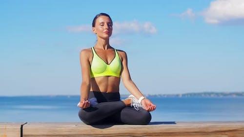 Young Woman Meditating in Lotus Pose at Seaside