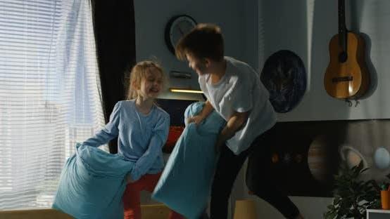 Thumbnail for Niño y niña jugando almohada lucha en la cama
