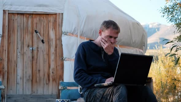 Man Freelancer Works Remotely Near Mongolian Yurt