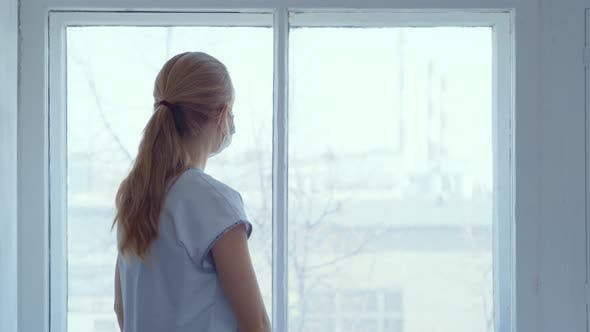 Thumbnail for Woman at Window with a Mask in Isolation for Virus Outbreak .