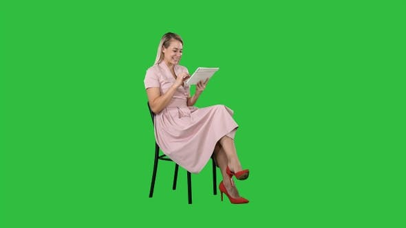 Thumbnail for Funny pretty young woman in pink dress sitting on a chair