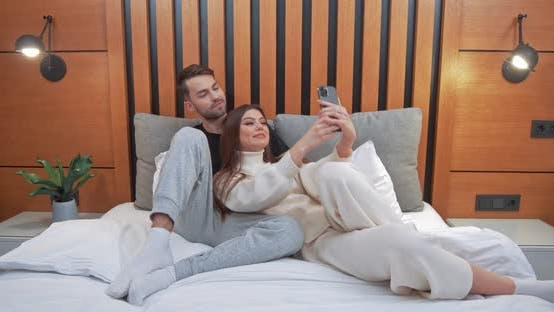Young Couple Takes a Selfie on a Smartphone Man and a Woman Lying on the Bed and Shoot a Video on a