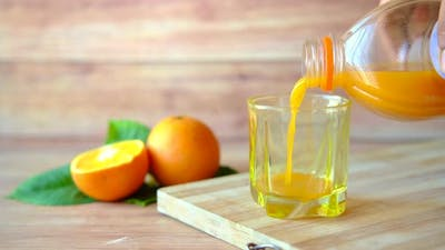 Fresh Orange and Glass of Juice on Table