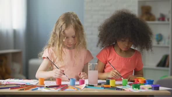 Cover Image for Attentive Caucasian and Afro-American Girls Painting at Art School, Leisure Time