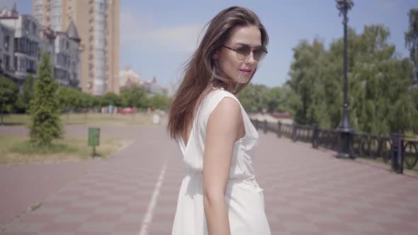 Cover Image for Portrait Young Girl Wearing Sunglasses and a Long White Summer Fashion Dress Walking