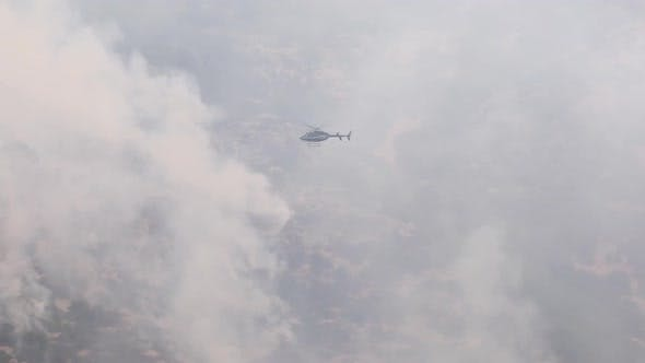Thumbnail for Helicopter flying through smoke of wildfire to survey the area
