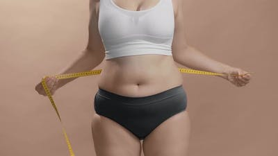 Overweight Woman in Underwear Measuring Her Fat Belly with Measure Tape