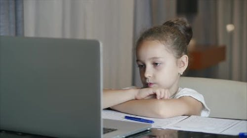 The Younger Student Sits at Home at the Computer, Studies, Listens To School Lectures, and Does His