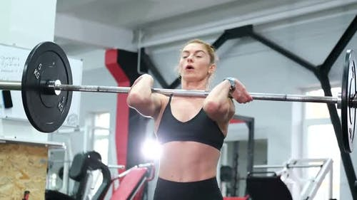 Athletic woman performs traction pose, performing exercises with a barbell