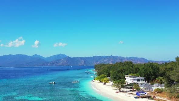 Daytime fly over clean view of a sunshine white sandy paradise beach and blue water background in hi