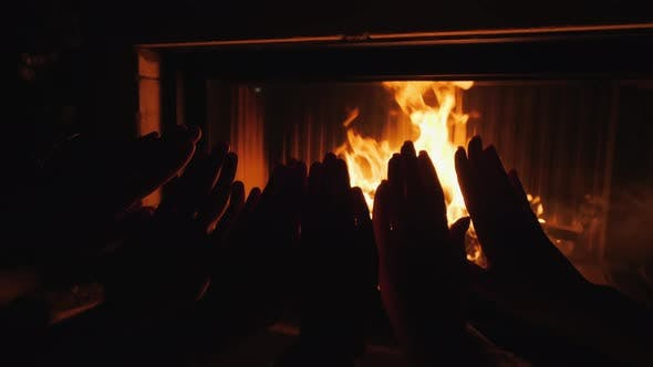 Thumbnail for Parents with a Child Warm Their Hands Together By the Fire of a Fireplace
