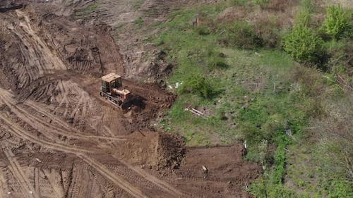 Aerial view of bulldozer flattening surface on further construction site