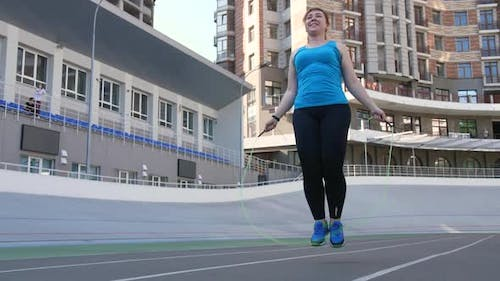 Overweight Female Jumping Rope on Sports Ground