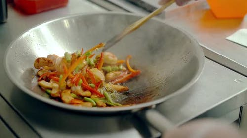 Cook Roasted Shrimps with Vegetables in a Frying Pan, Mixed Them with a Wooden Spatula.