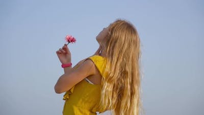 Teen Bends Over with a Flower in Her Hand in Slow Motion