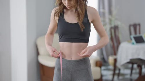 Unrecognizable Young Slim Woman Measuring Waistline Indoors