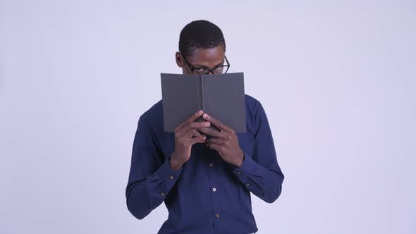 Thumbnail for Young African Nerd Businessman with Eyeglasses Covering Face with Book