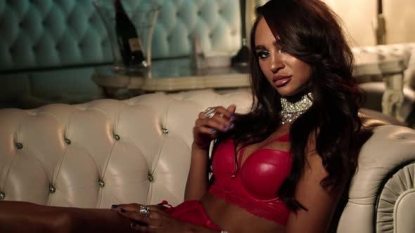 Sexy Frau streicheln ihren perfekten Körper In Roter Unterwäsche Und Flirten Mit Der Kamera.