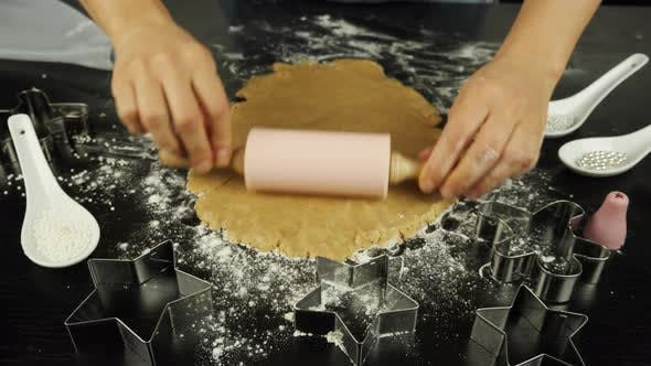 Hands are rolling raw dough with rolling pin on black wood table in modern kitchen