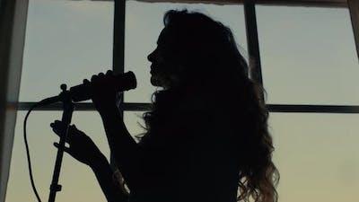Woman Singing Song in Microphone. Singer Performing Musical Song in Microphone