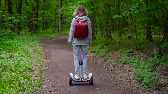 Thumbnail for A Woman Rides Along a Forest Path on an Electric Gyrocopter. The Girl Has a Red Backpack and Light