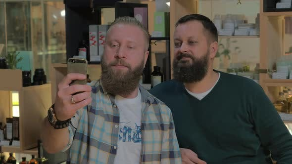 Two bearded men taking mobile selfie indoor