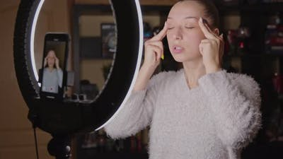 Young Female Blogger Doing Face Fitness Exercises at Home, Live Streaming