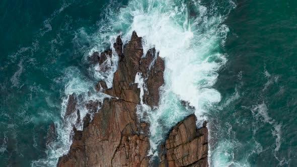Ocean Waves Crash Against Stony Rocks During Sunset on the Island of Sri Lanka