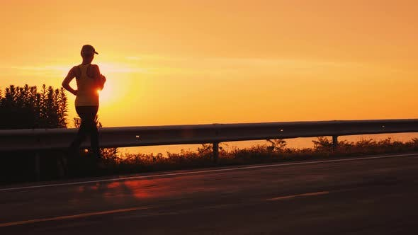 Thumbnail for Slim Athletic Woman Running Along the Road Against the Orange Sky and the Setting Sun