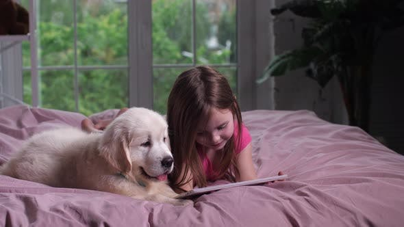 Thumbnail for Joyful Child Watching Youtube on Tablet with Puppy