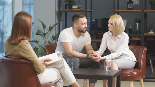 Smiling Couple Talking To Professional Psychologist and Solve Relationship Problems.