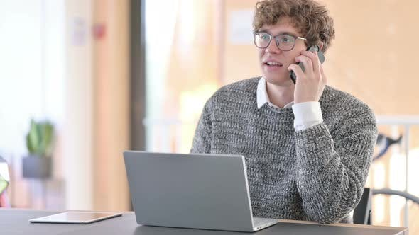 Thumbnail for Young Man with Laptop Talking on Smartphone at Work