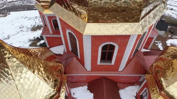 Thumbnail for Luftaufnahmen auf der ukrainischen Kirche mit goldenen Kuppeln im Karpatendorf im Winter