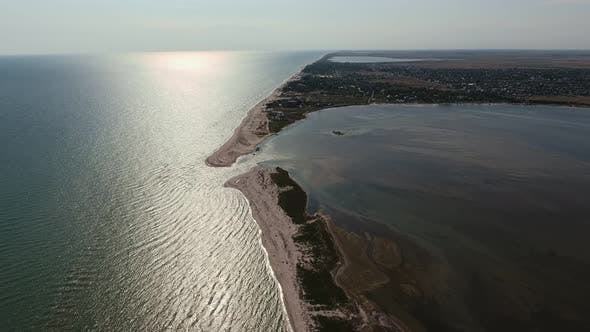 Thumbnail for Aerial Shot of Upright Sandspit Touching a Curvy Stripe at Sunset in Summer