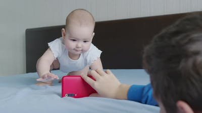 Adorable Baby Infant Girl Looks with Interest at the Mobile Phone