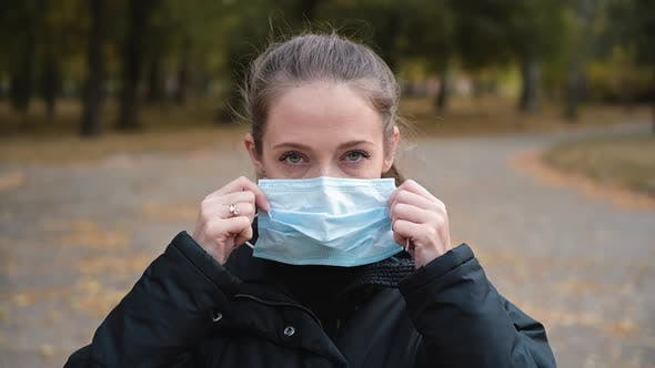 Thumbnail for Woman Putting on Medical Mask for Coronavirus Protection Outdoors